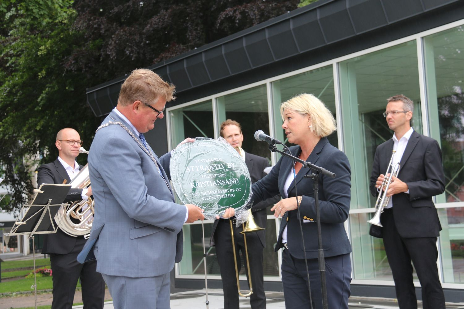 Monica Mæland, minister of Local Government and Modernisation, presented the award to Mayor of Kristiansand, Harald Furre. In the background, musicians from Kristiansand Symphony Orchestra (KSO)
